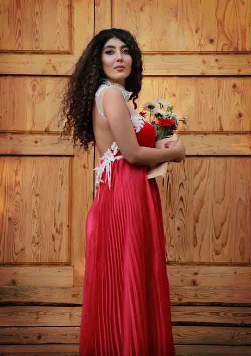 Woman in Red Sleeveless Dress Holding Bouquet of Flowers
