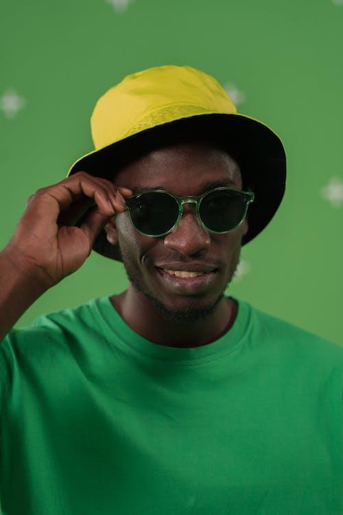 Man in Green Crew Neck Shirt Wearing Black Sunglasses and Yellow Cap