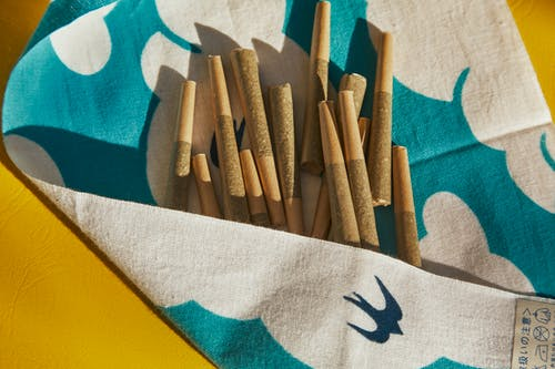 Brown Wooden Sticks on White and Blue Textile