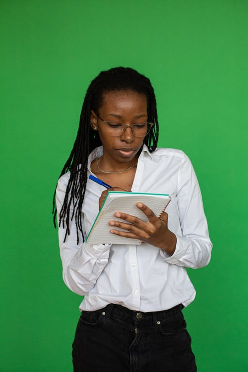 Woman in White Dress Shirt Holding White Tablet Computer