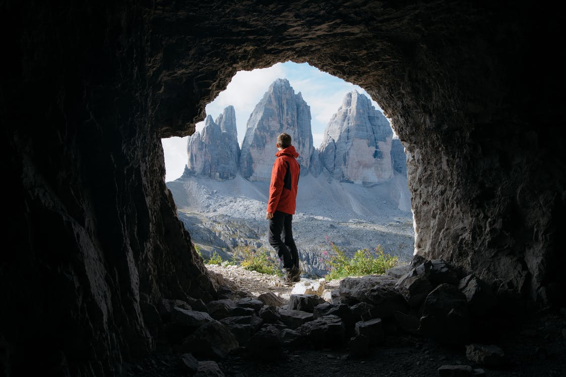 Man in Red Jacket Standing Outside of Cave in Front of Three Mountains
