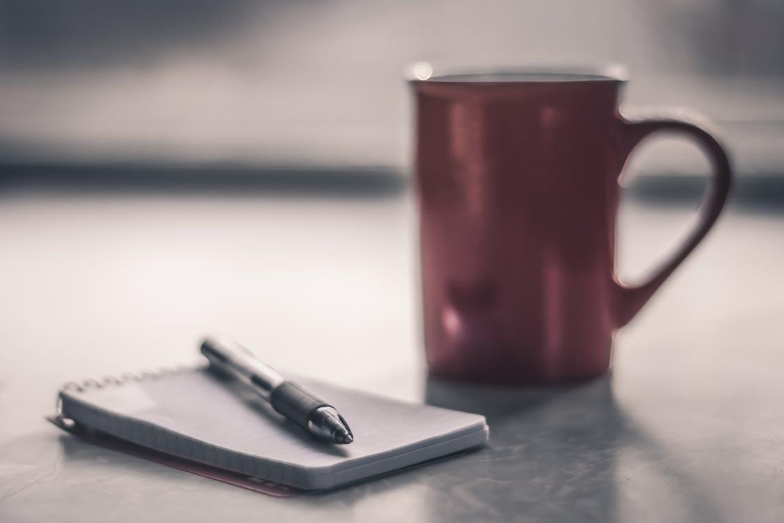 długopis, filiżanka kawy, kubek