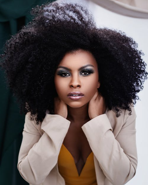 Woman in White Blazer With Black Curly Hair