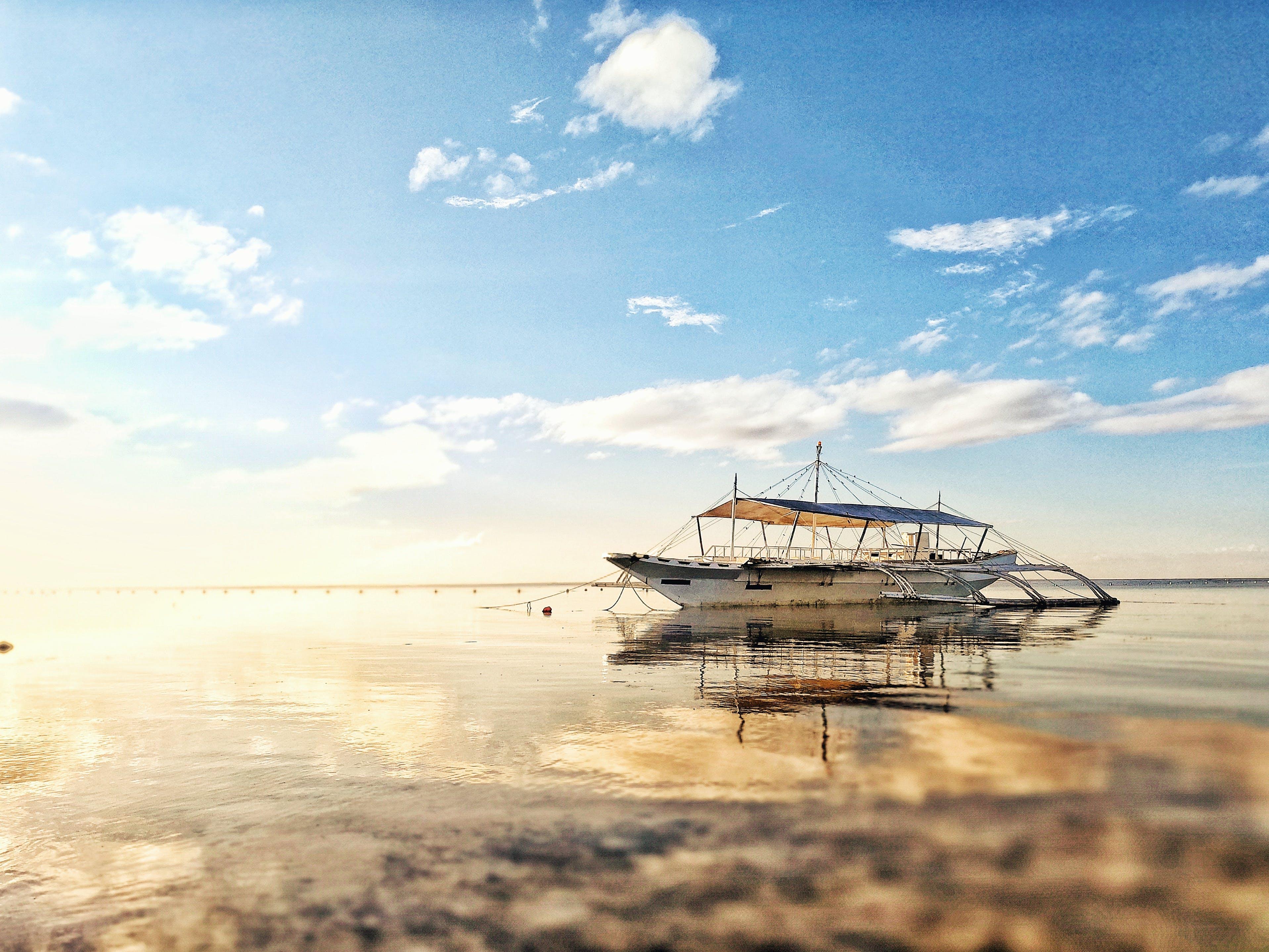 White Boat on Sea during Sunrise