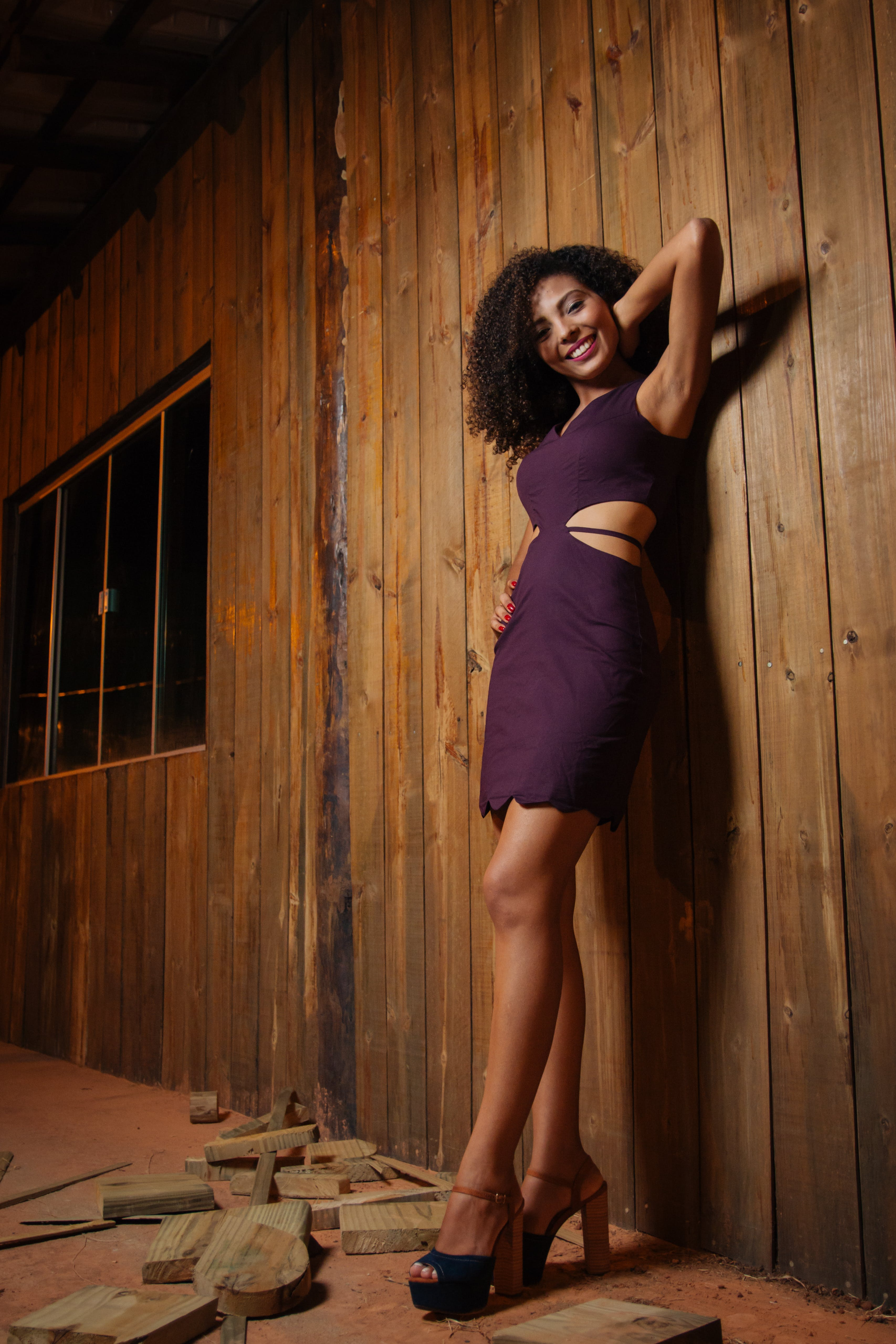 Woman Wearing Purple Sleeveless Mini Dress Leaning on Brown Wall