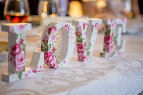 Decoration in love shaped form on table with food and wine glasses during celebration