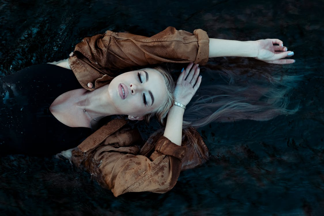 A Woman in a  Brown Jacket Lying on Water