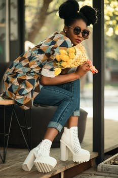 Woman Wearing White-green-yellow Geometric Sleeved Shirt, Blue Denim Pants and White Block Heeled Booties