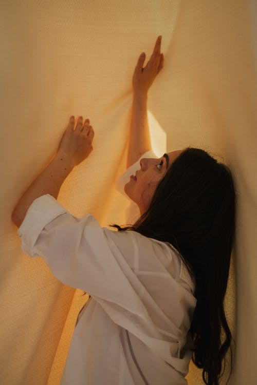 Woman in White Long Sleeve Shirt Lying on Bed