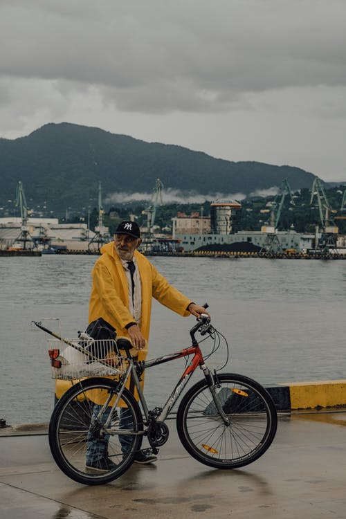 Man in Yellow Dress Shirt and Black Pants Standing Beside Black Bicycle