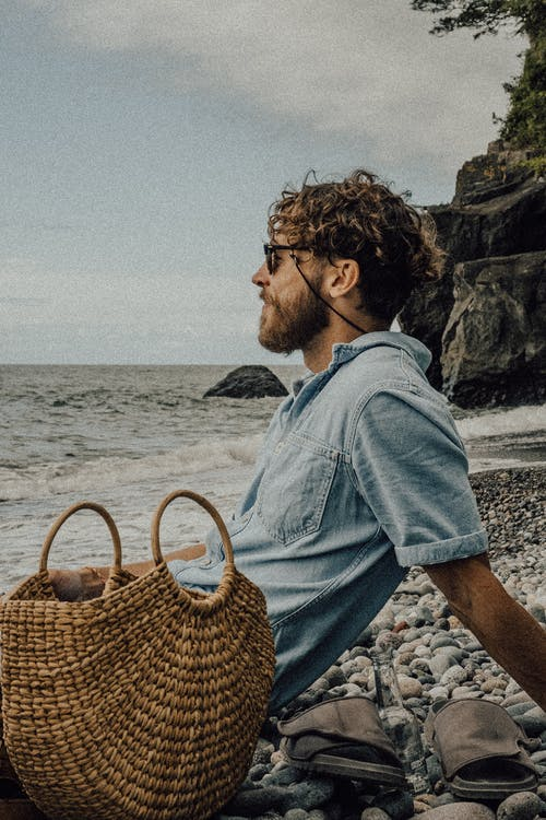 Man in Blue Dress Shirt Sitting on Beach With Brown Woven Basket on His Back