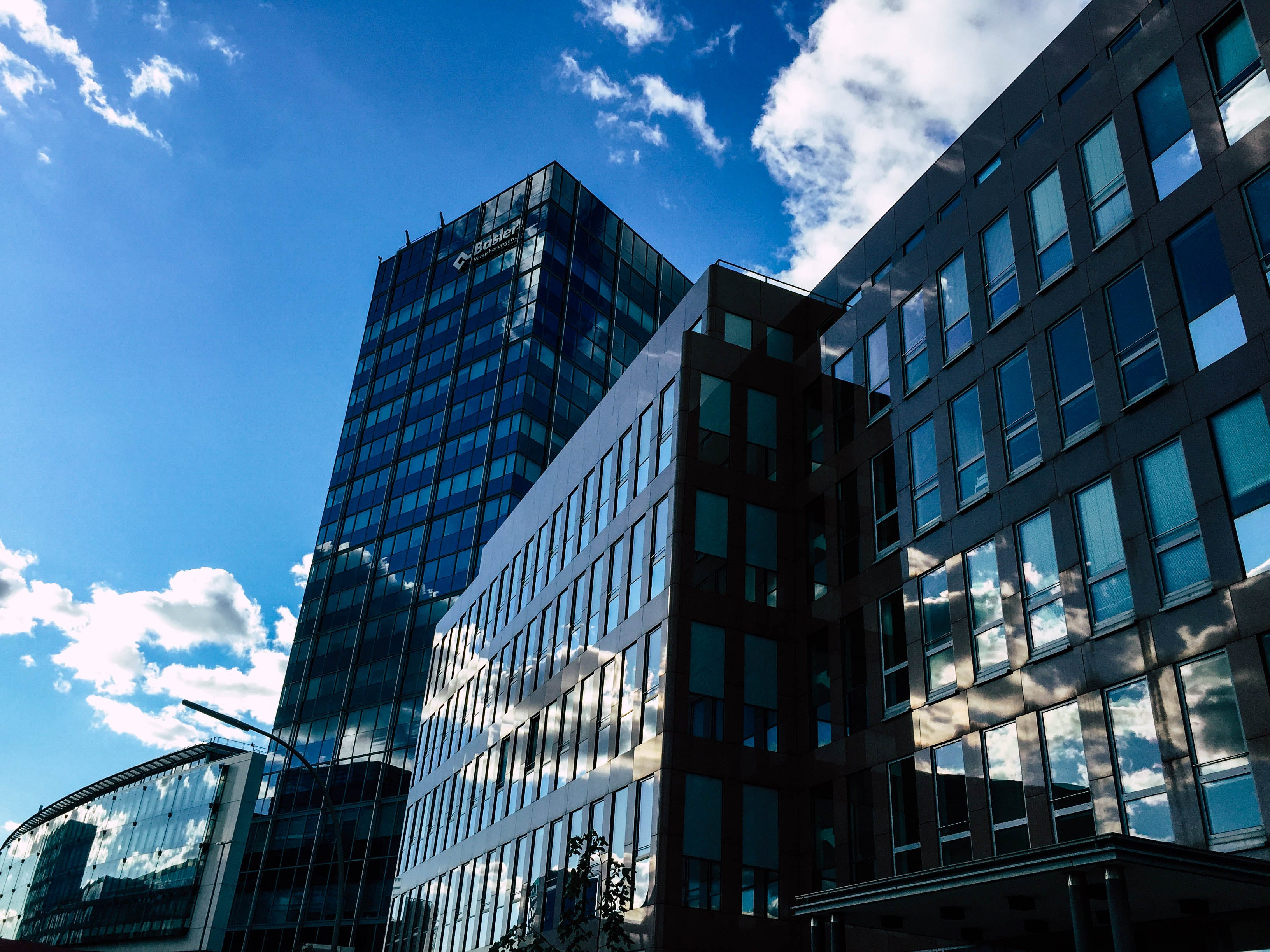 Low-angle Photography of Curtain Wall Building Taken Under White Clouds and Blue Sky