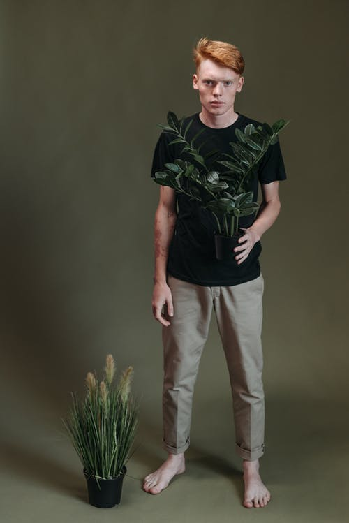 Man in Green and Black Camouflage Crew Neck T-shirt and White Pants Standing Beside Green