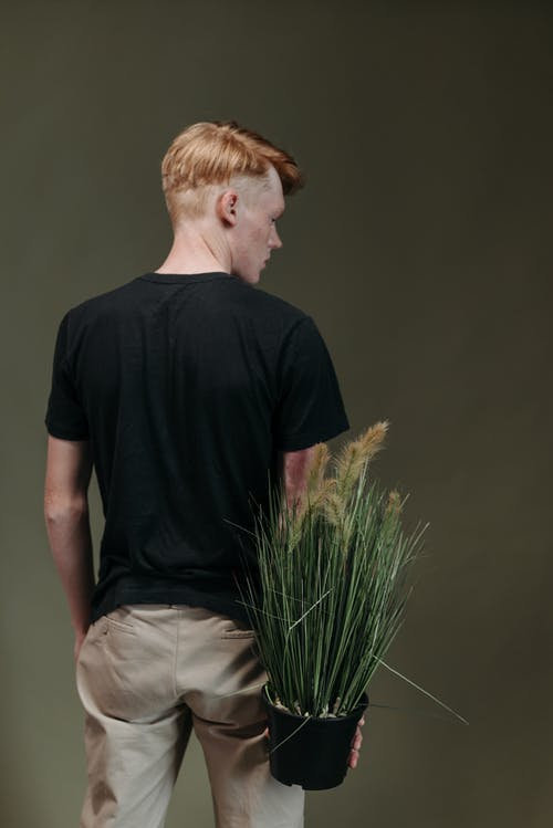Man in Black Crew Neck T-shirt and White Pants Sitting on Green Grass