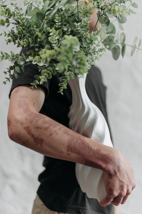 Man in Black T-shirt Holding Green Plant