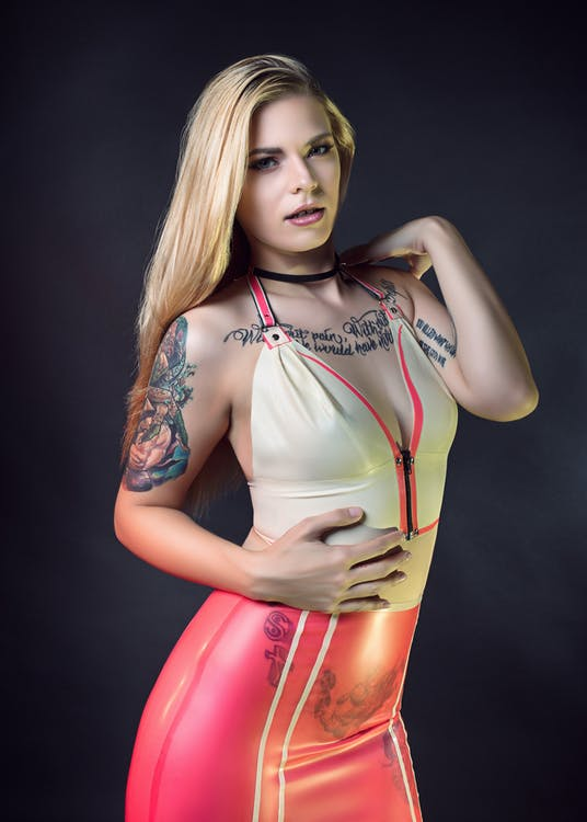 Standing Woman Wearing Beige and Pink Halter-strap Top and Pink Bottoms Holding Right Hand on Tummy