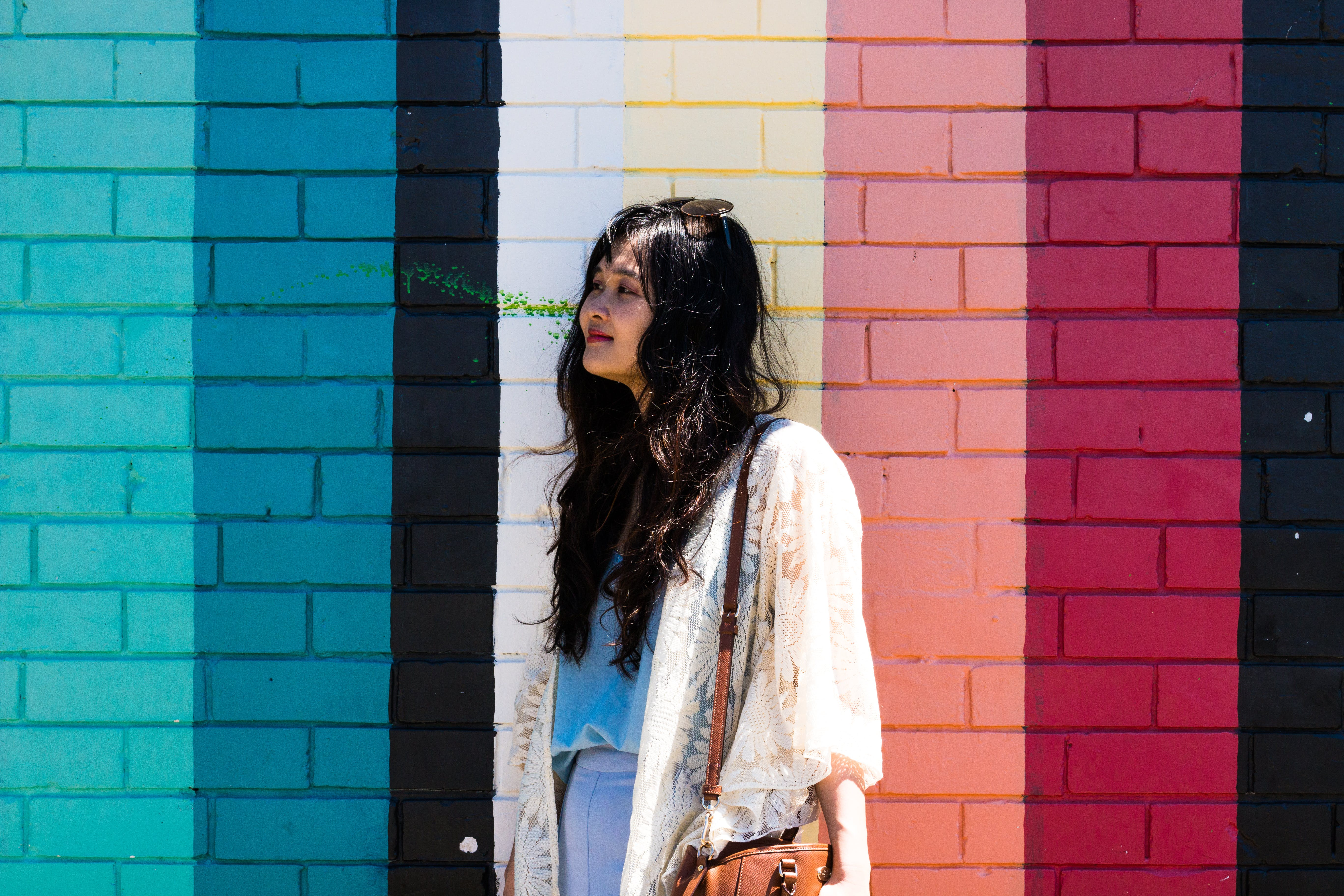 Woman Wearing White Cardigan Standing Beside Multicolored Wall