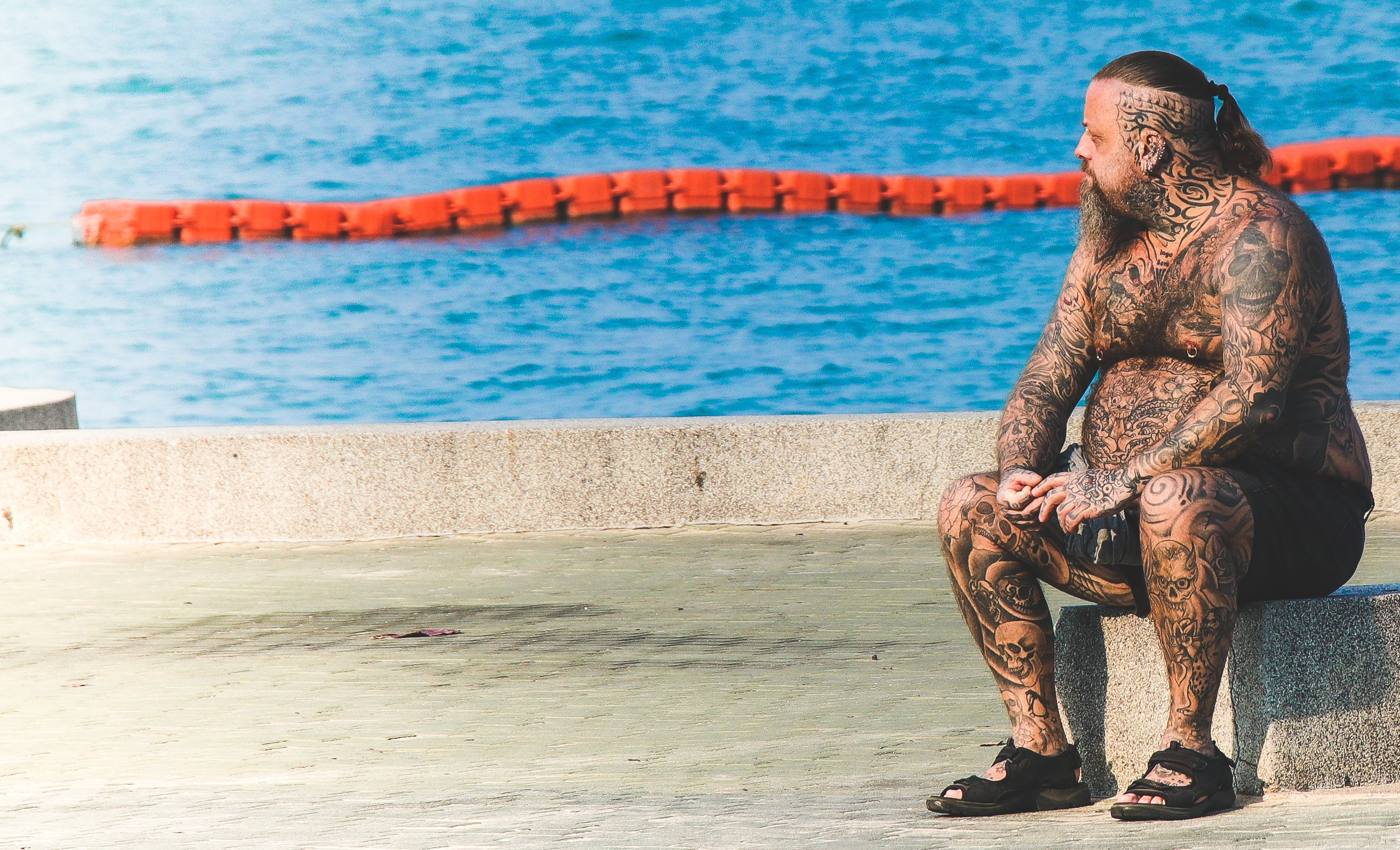 Man With Tattoos Sitting on Gray Concrete Floor Near Body of Water