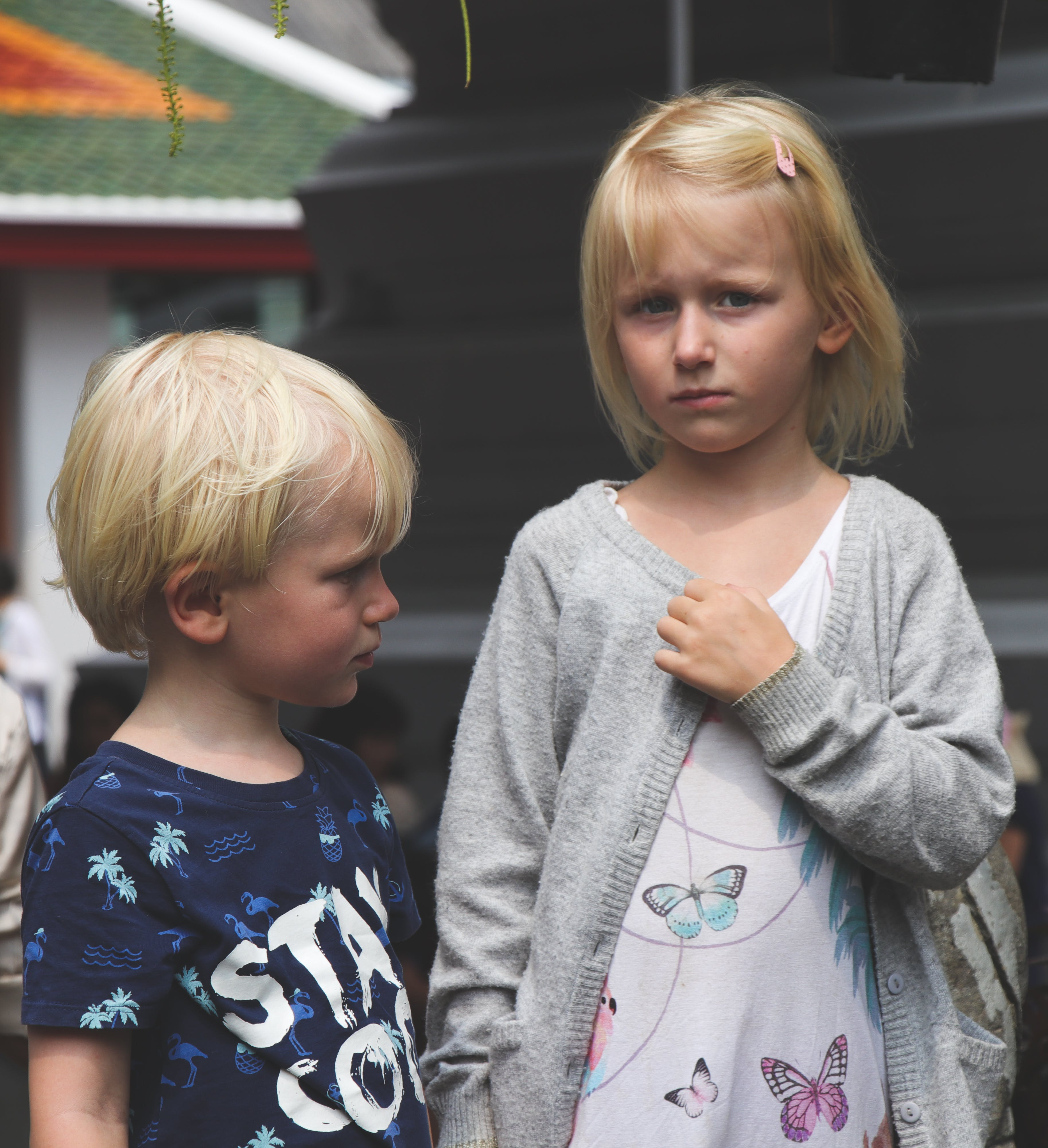 Boy Wearing Blue and White Stay Cool Print Crew-neck T-shirt Next to Girl Wearing White and Teal Butterfly Printed Scoop-neck Shirt and Gray Open Long-sleeved Cardigan