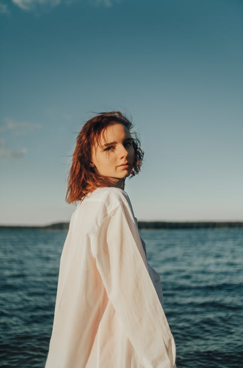 Woman in White Long Sleeve Shirt Standing Near Body of Water
