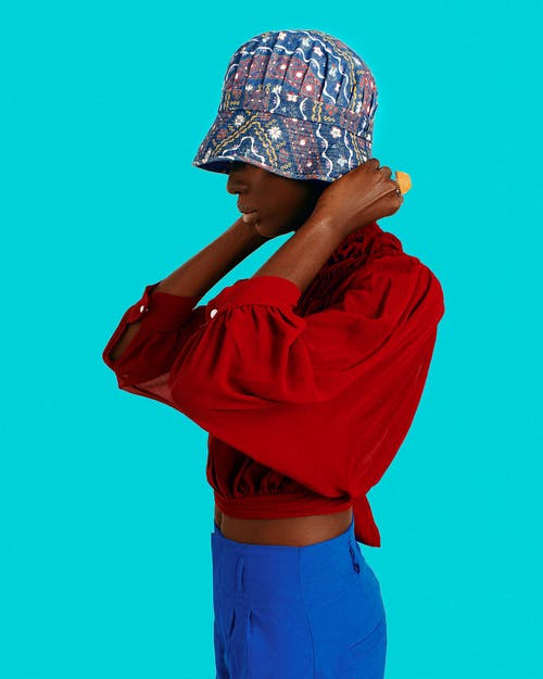 Woman in Red Jacket Covering Her Face With Blue and White Floral Cap