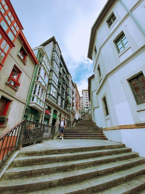 People Walking on Stairs Between Concrete Buildings