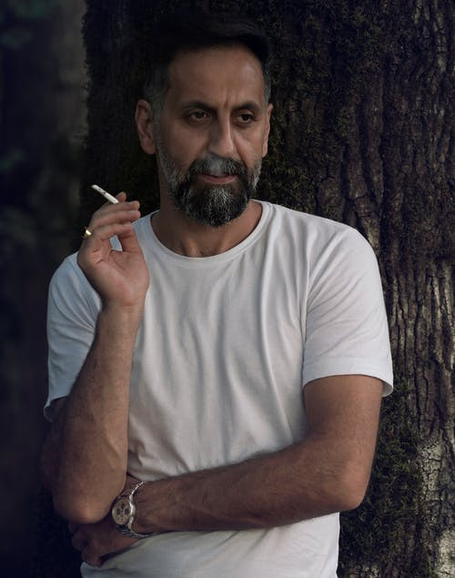 A Bearded Man in a White Shirt Smoking a Cigarette