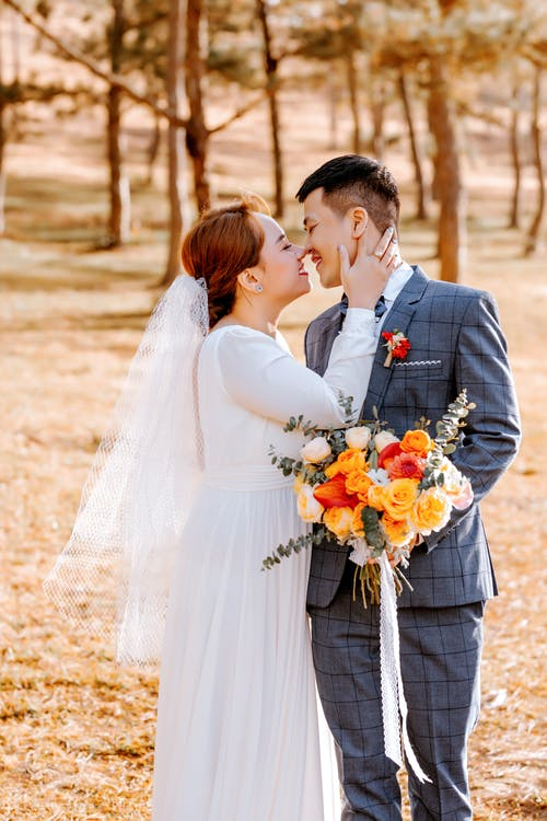 Man in Black Suit Kissing Woman in White Wedding Dress Holding Bouquet of Flowers