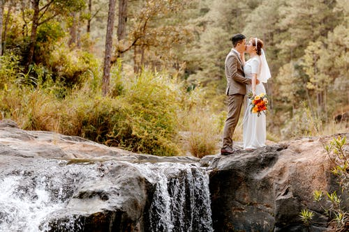 Bride and Groom Standing on Rock