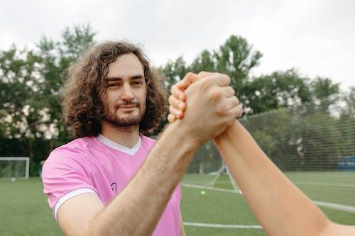 Photos gratuites de barbu, chemise rose, cheveux bouclés