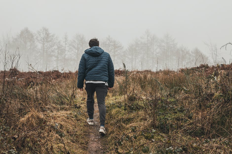 Man Wearing Blue Bubble Hoodie Jacket Walking on Green Grass Field