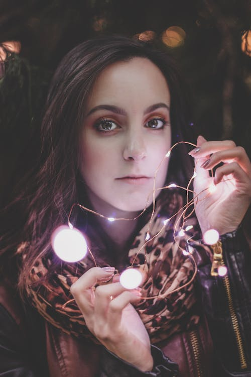 Woman Wearing Leather Jacket And Leopard Print Scarf Holding String Light