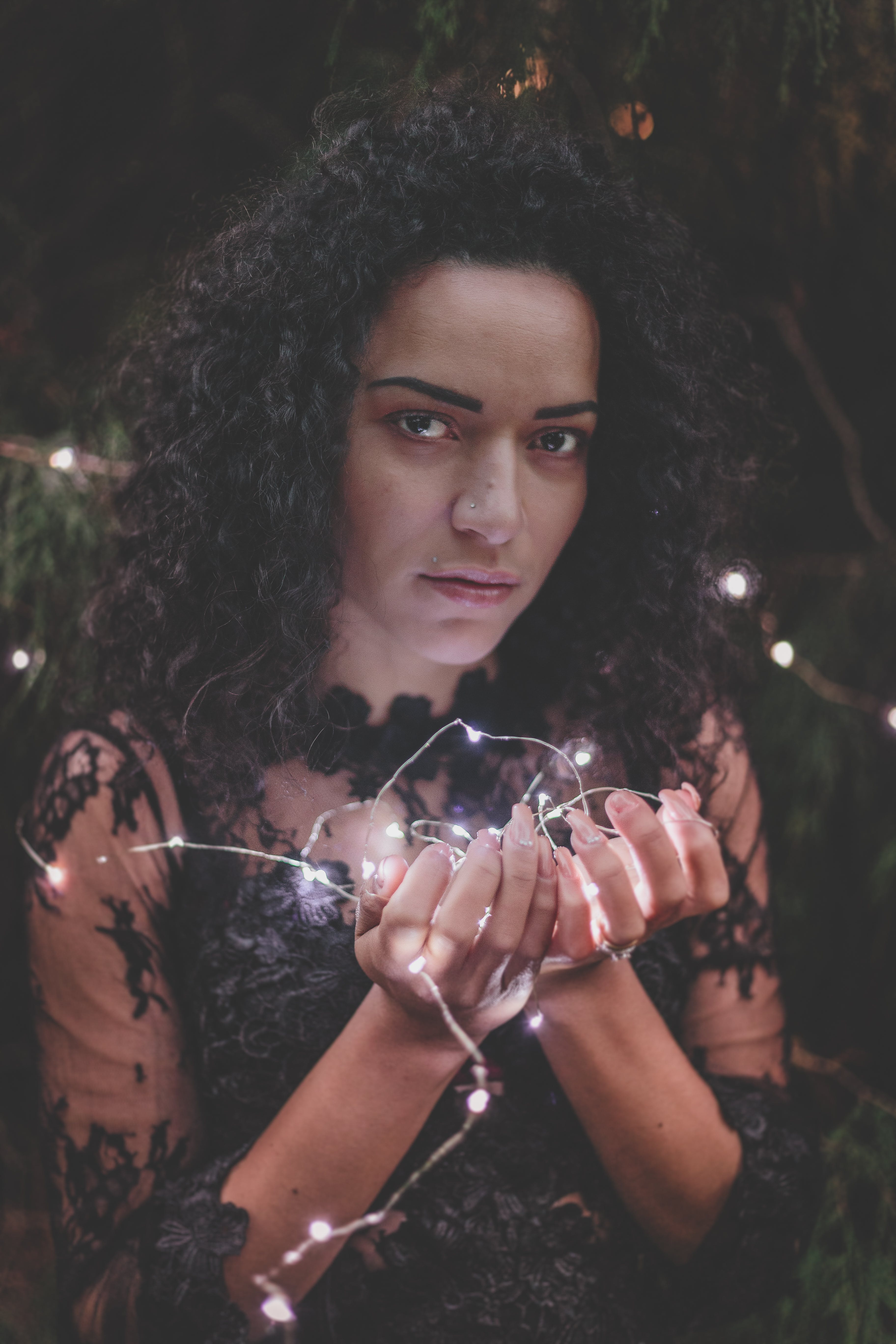 Woman In Black Lace Dress Holding String Lights