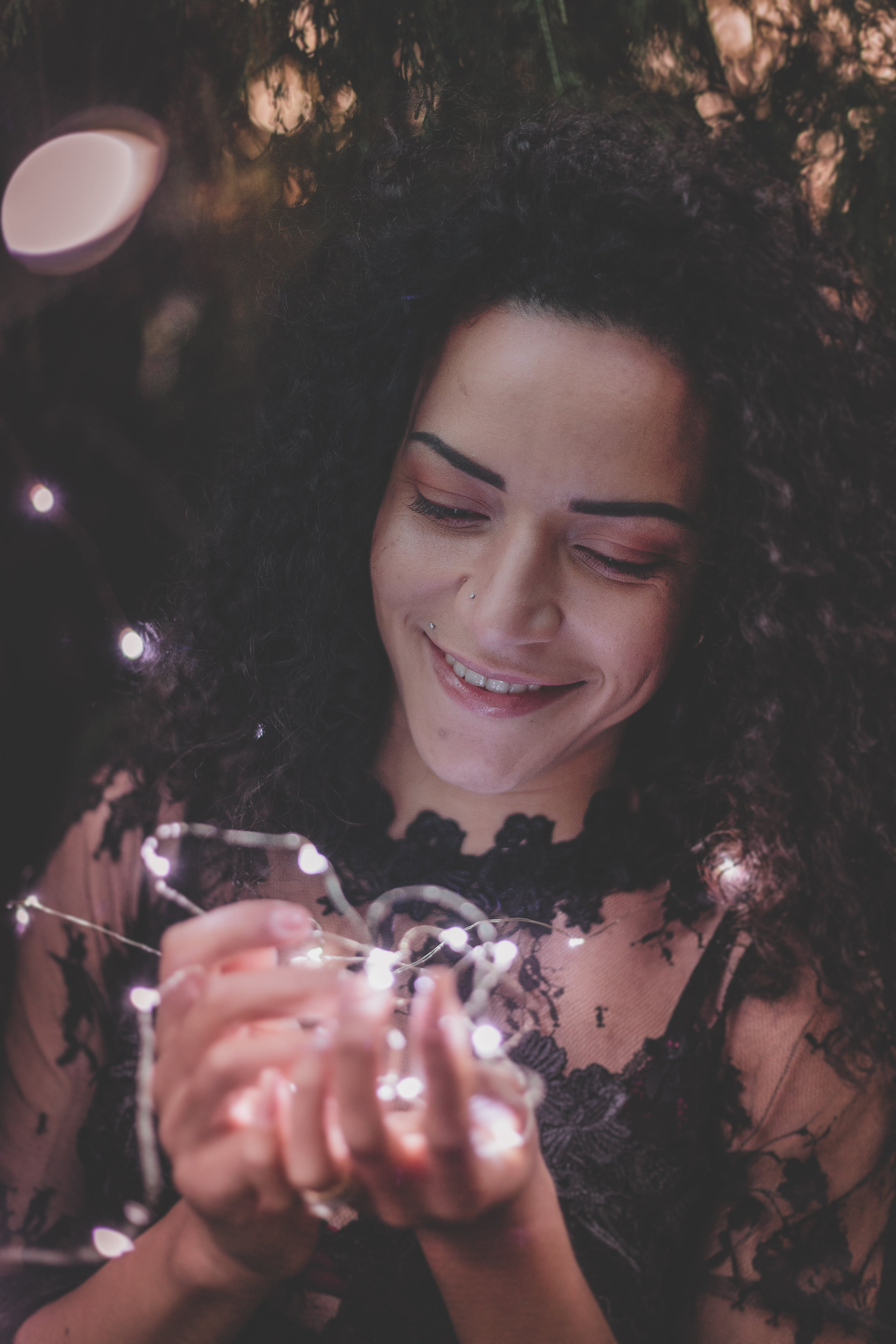 Woman Holding String Lights While Smiling