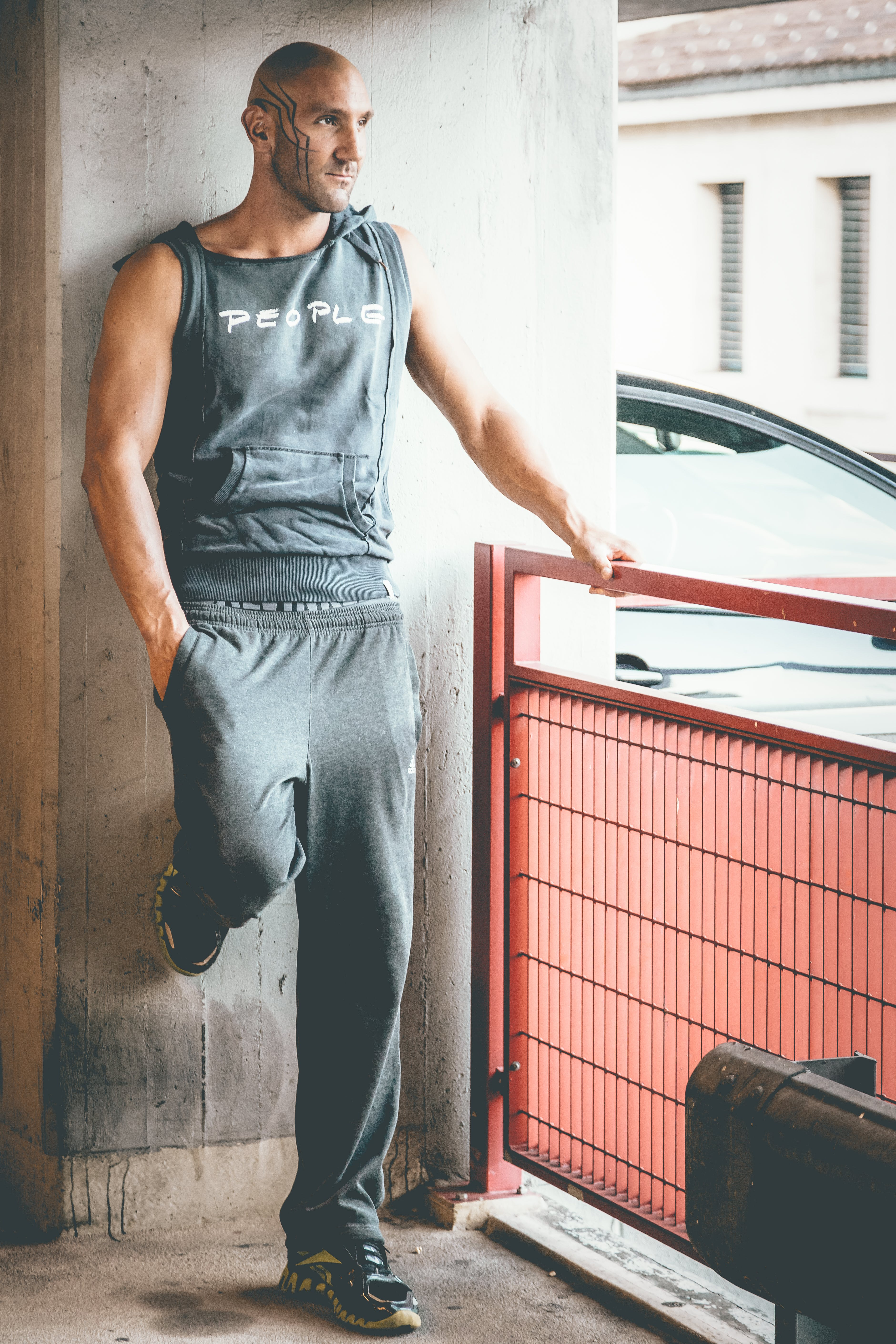 Man Wearing Gray Tank Top and Track Pants Leaning on Wall