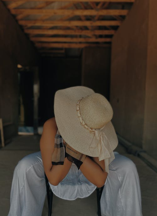 Woman in White Shirt and Brown Sun Hat Sitting on Floor