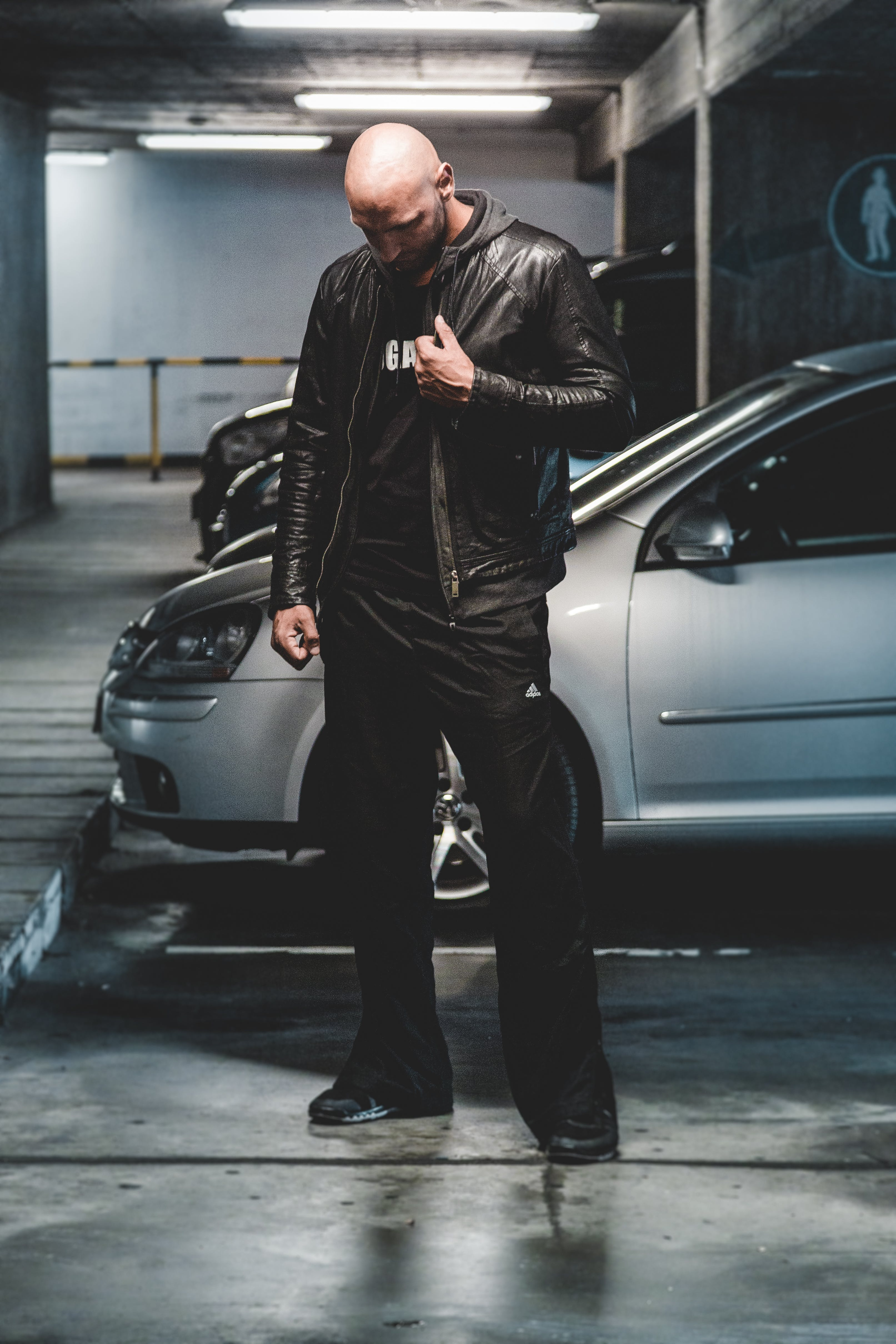 Man in Black Leather Jacket Standing in Front of Gray Car