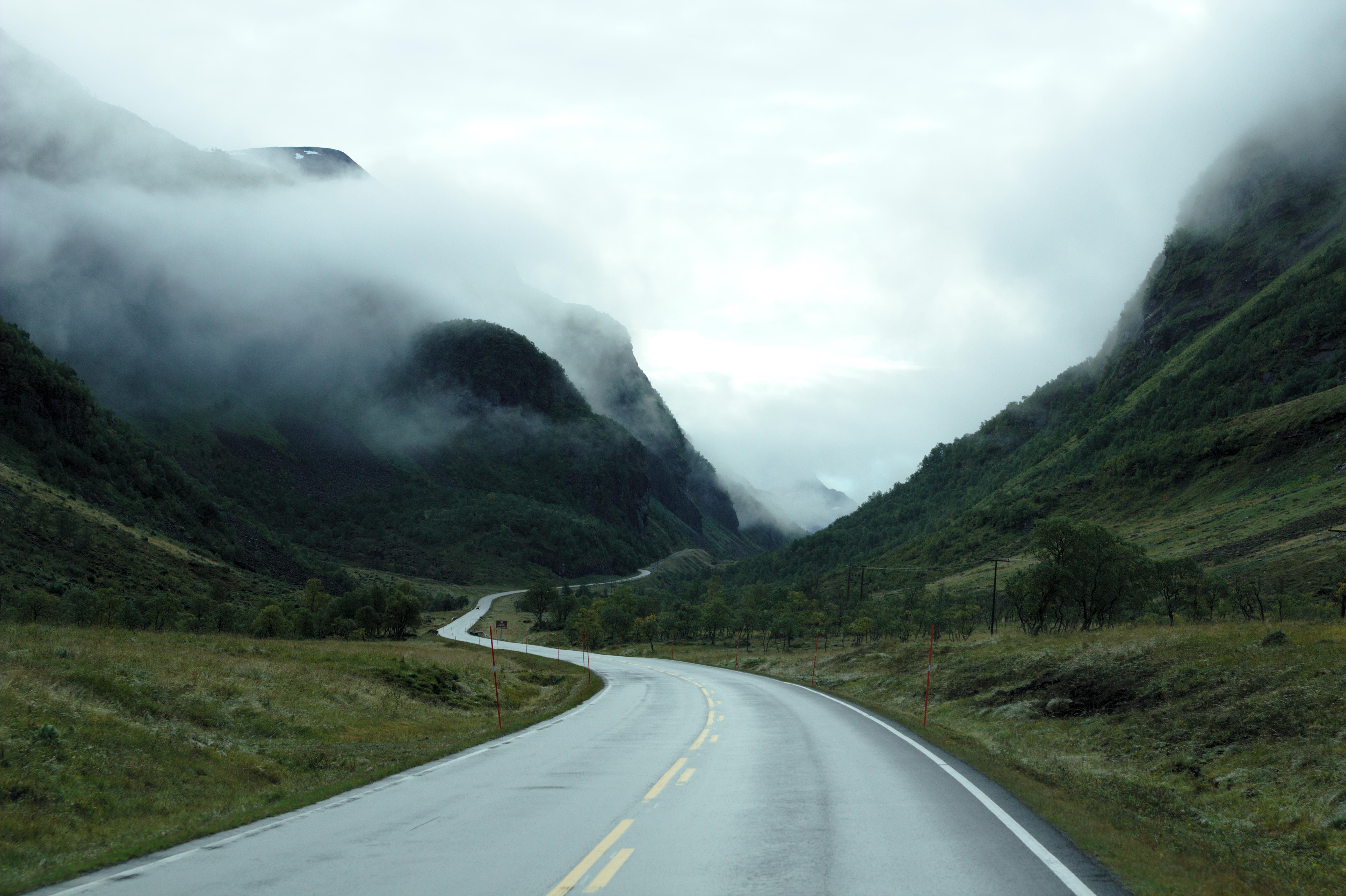 Gray Concrete Road Between Green Mountains Under White Clouds