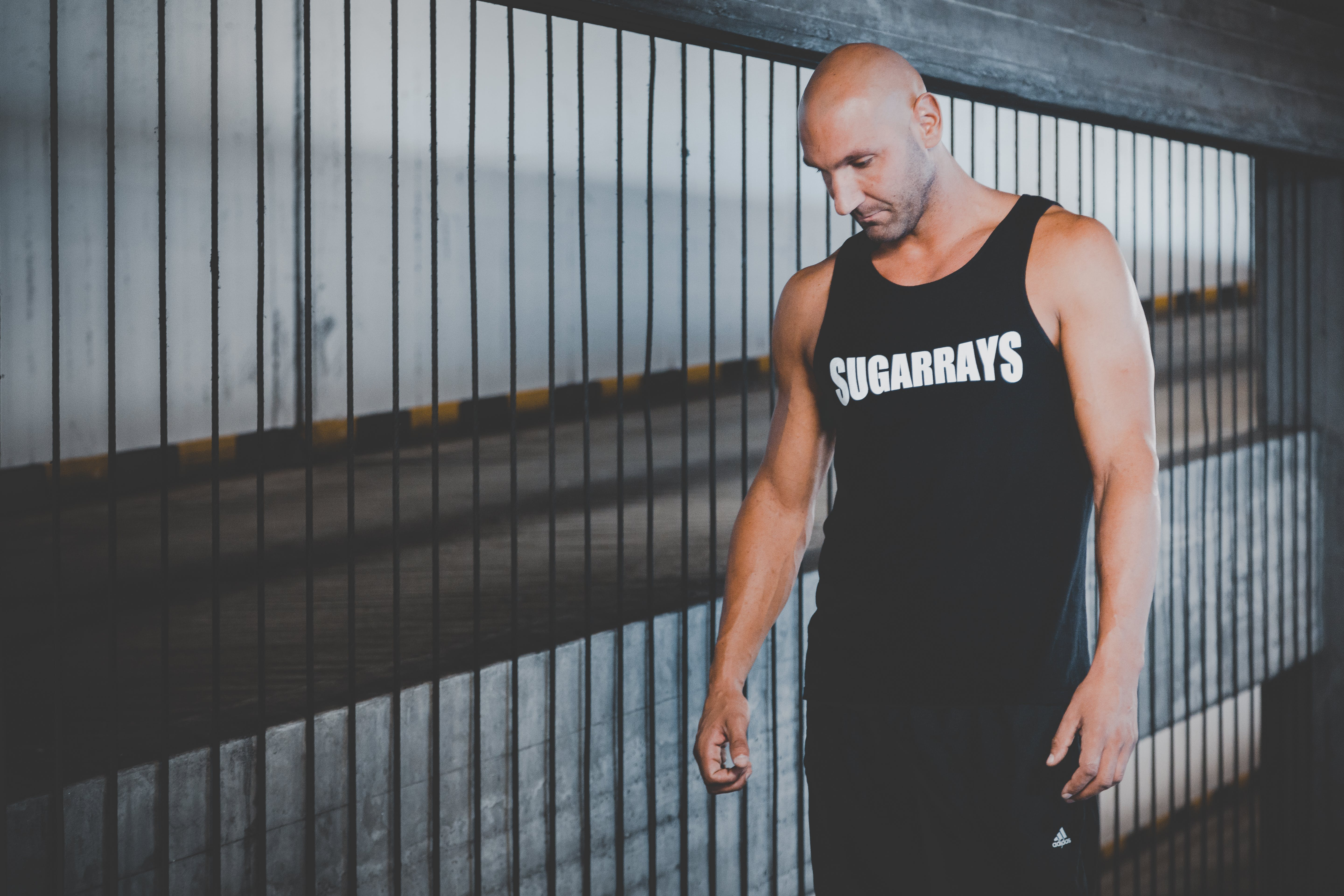 Man Wearing Black Tank Top Standing Near Black Metal Railings