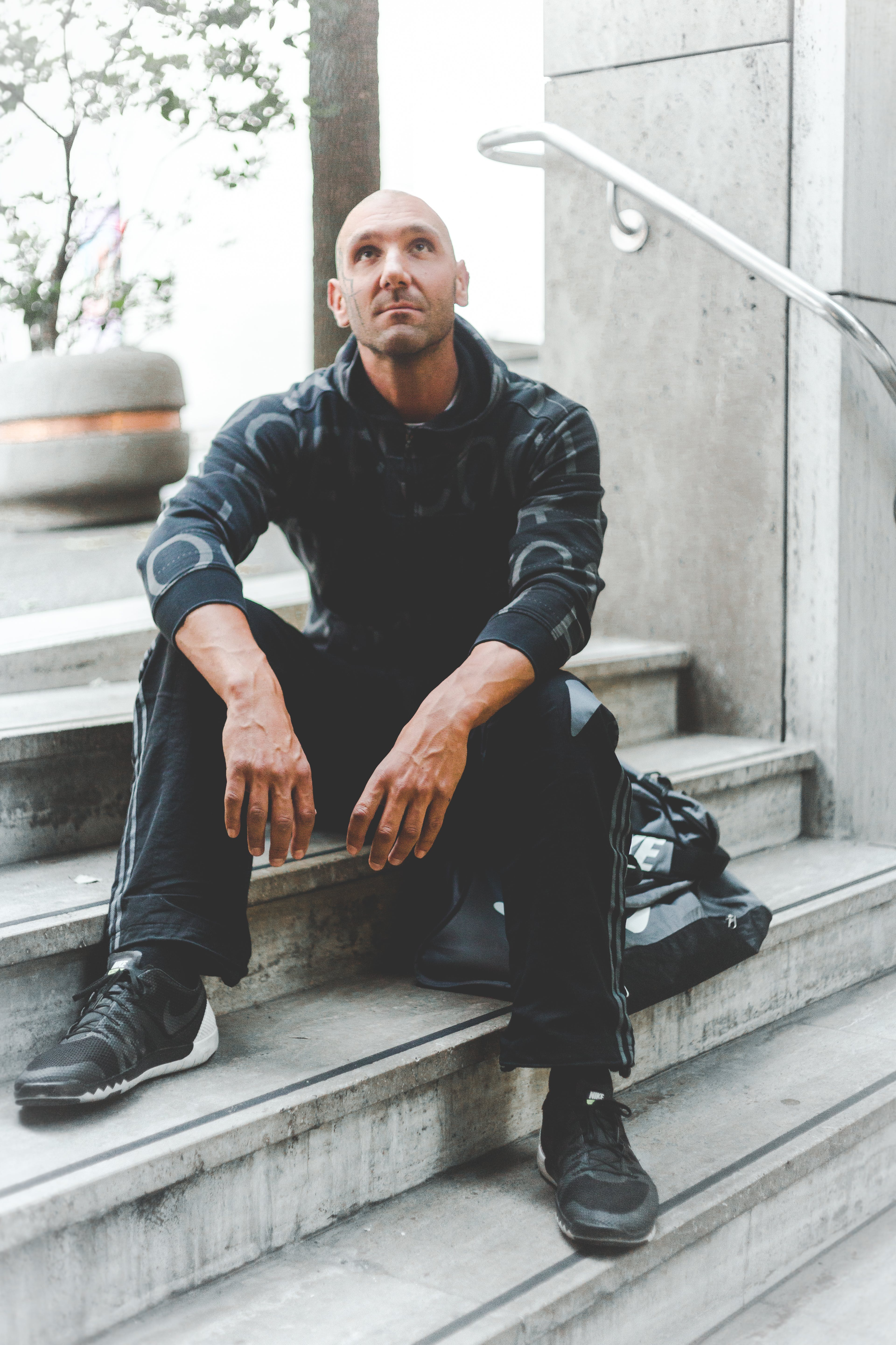 Man Sitting on Concrete Stair Looking Up