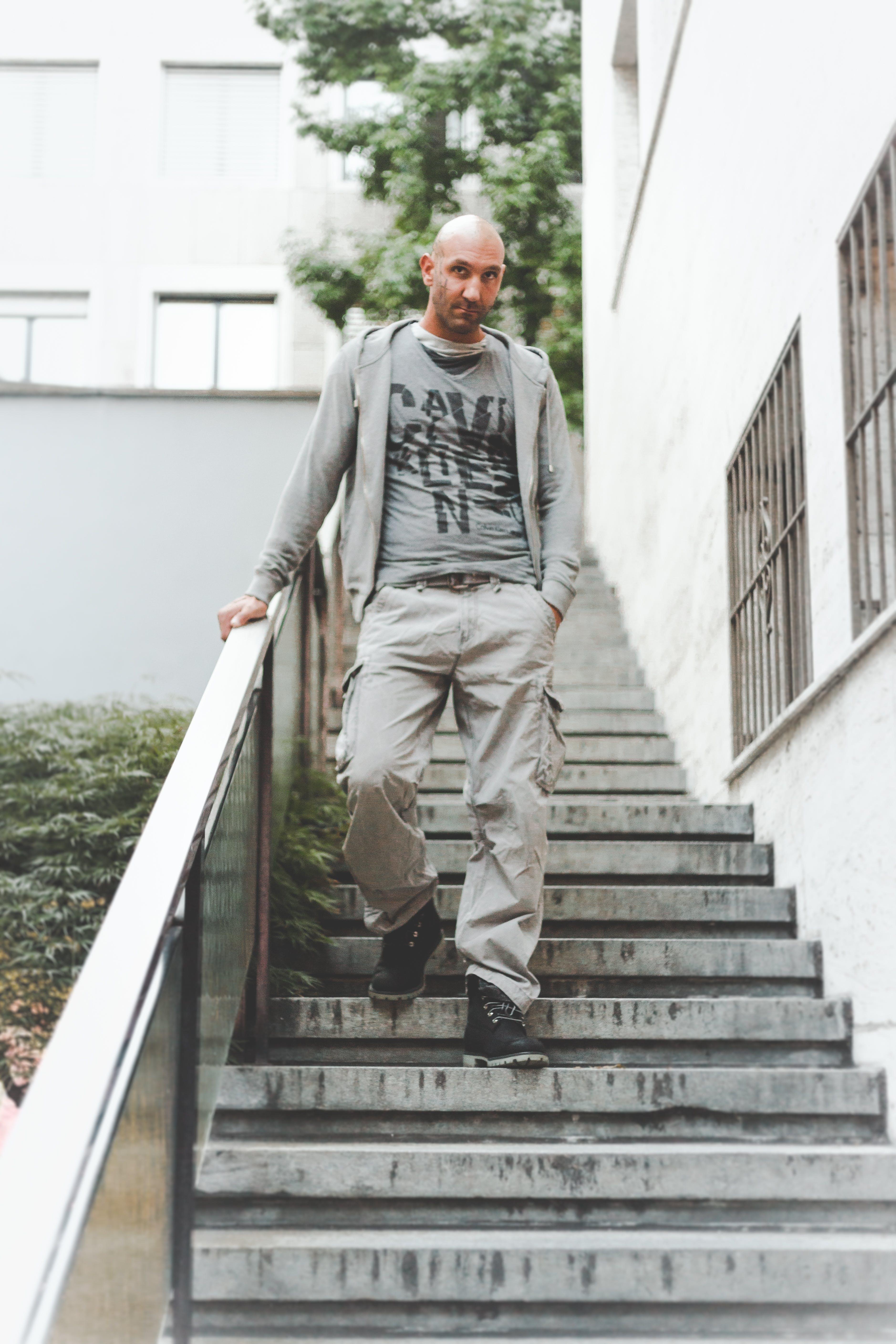 Man Wearing Gray Jacket Standing on Stair
