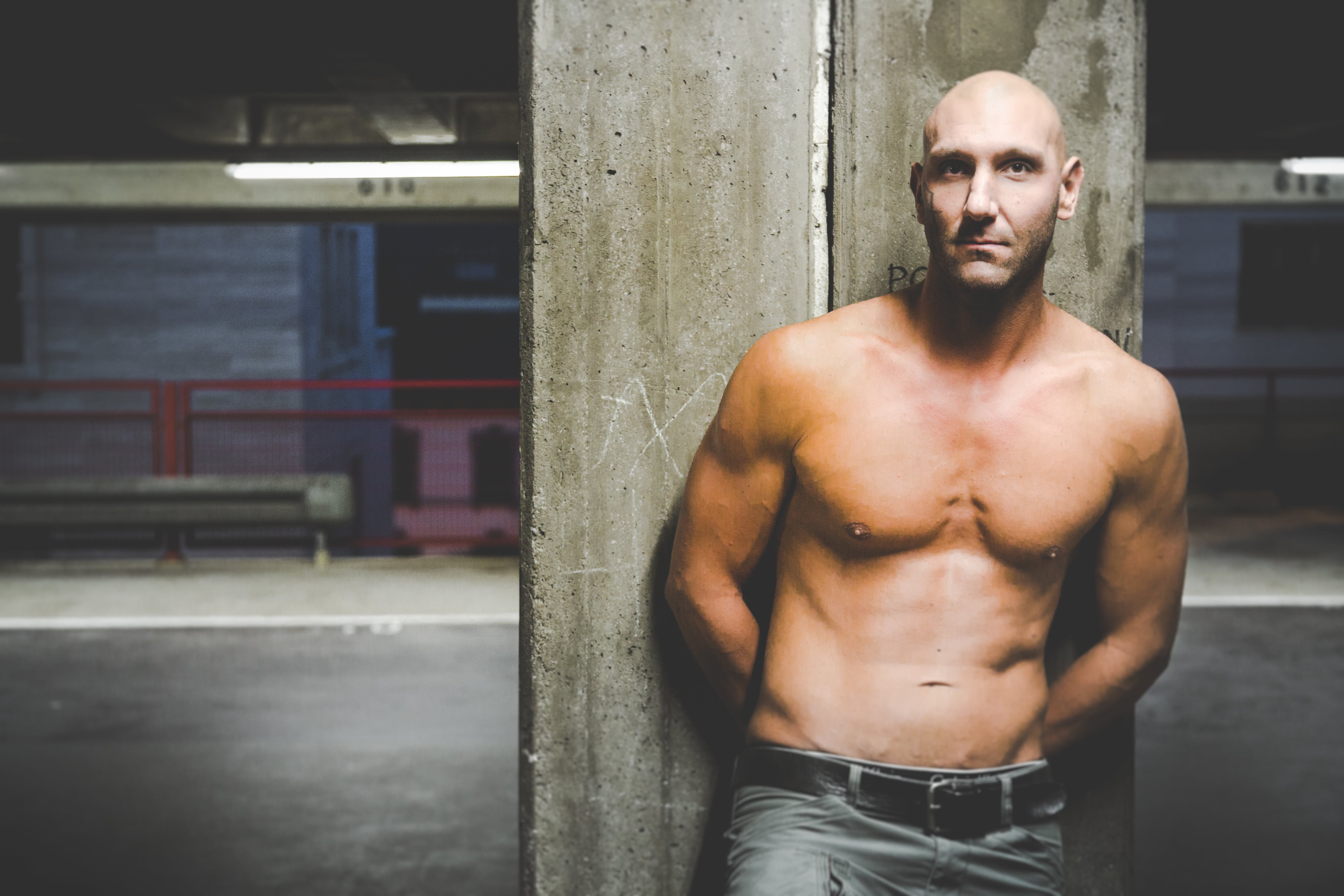 Photography of a Shirtless Man Leaning on Wall