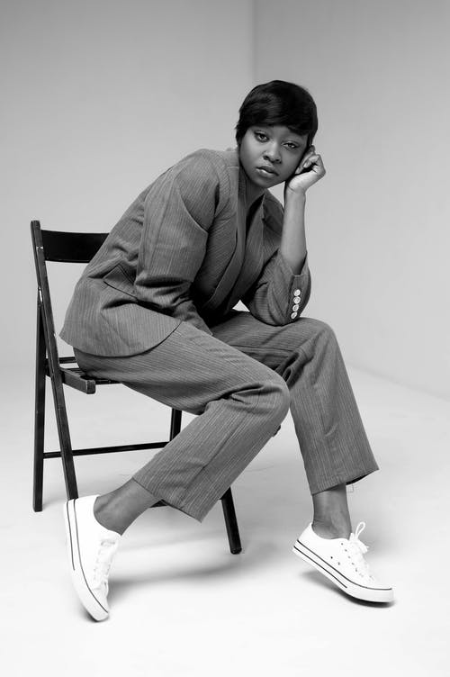 Grayscale Photo of Woman in Formal Suit Sitting on Folding Chair