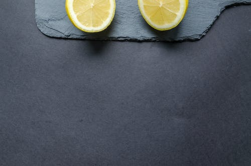 Two Sliced Lemons on Black Surface