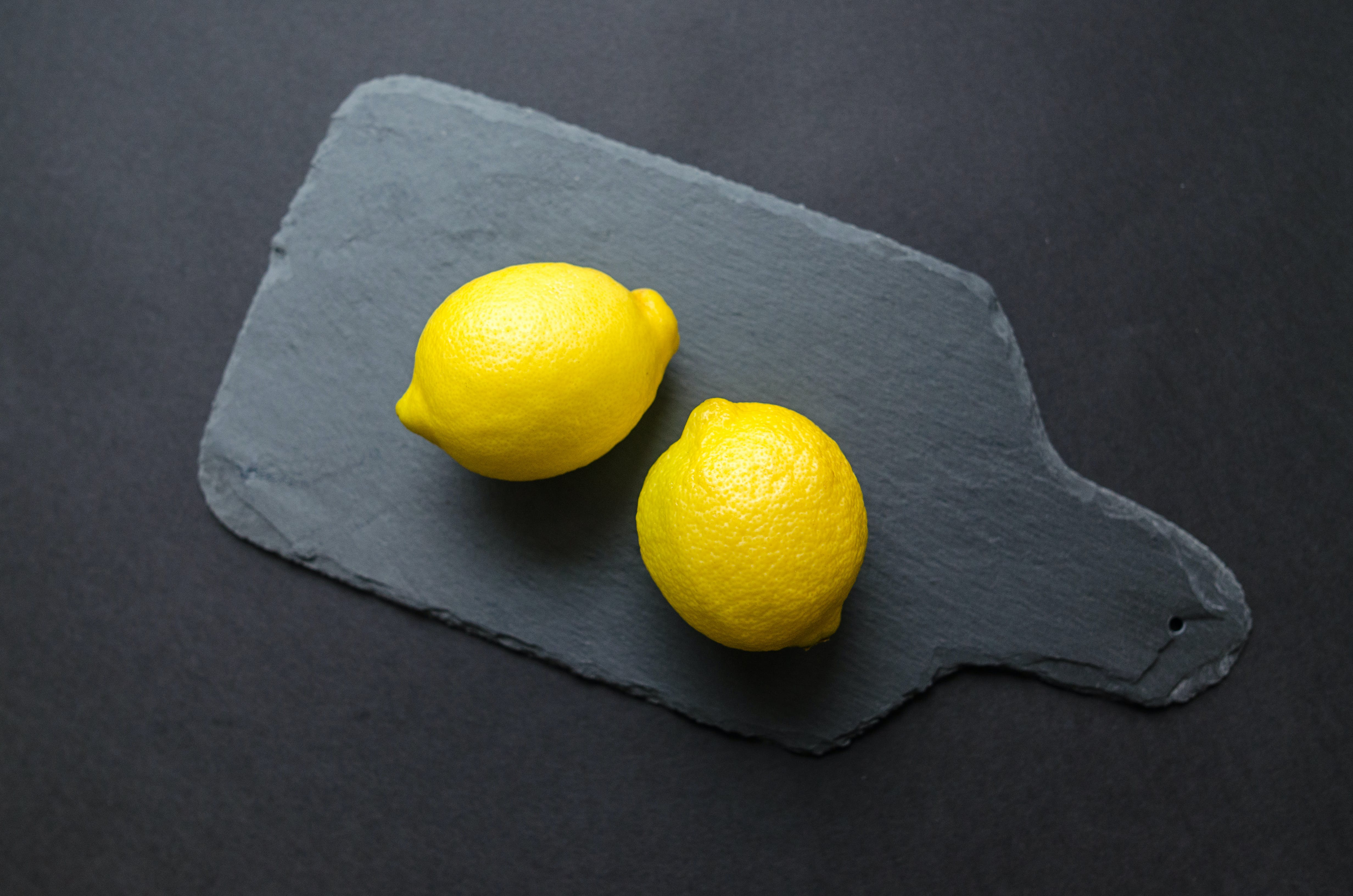 Two Lemons on Black Wooden Pad