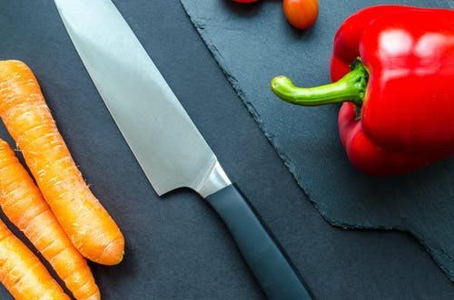 Black Handled Gray Kitchen Knife Beside Orange Carrots and Red Bellpepper