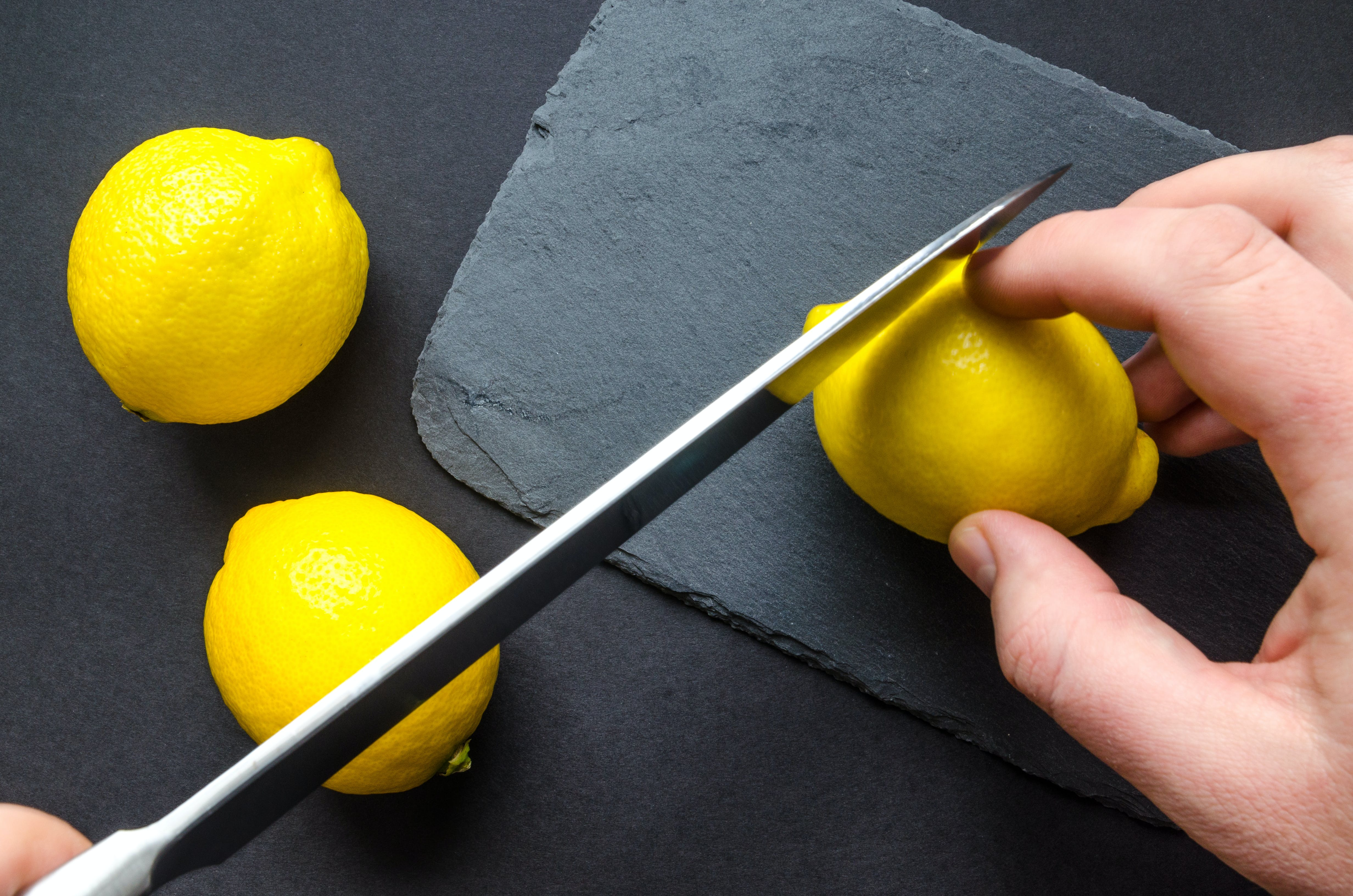 Human Slicing Yellow Lemon