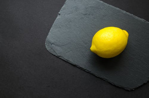 Photo of Yellow Lemon on Gray Surface