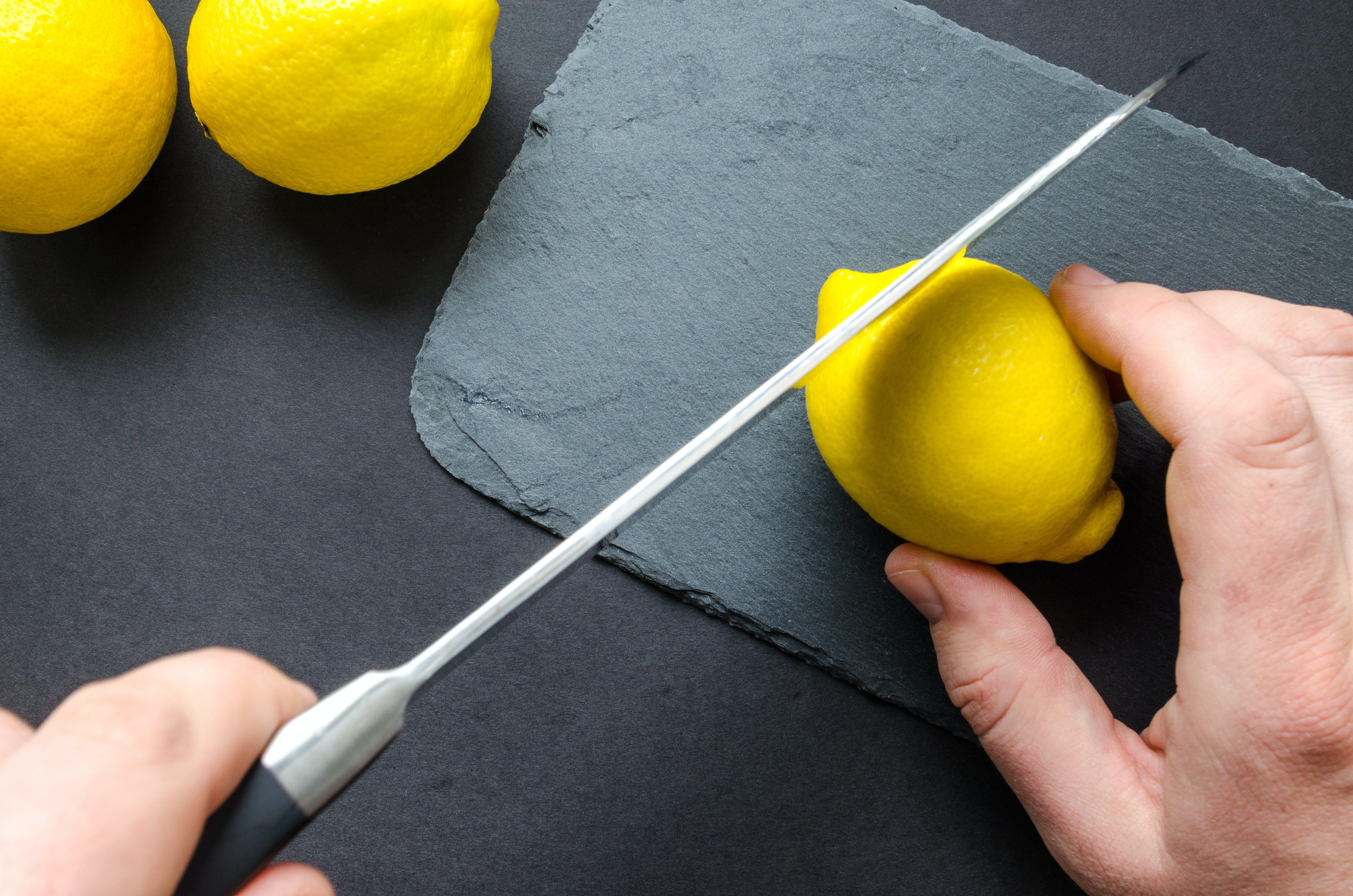 Photo of Person Slicing Lemon