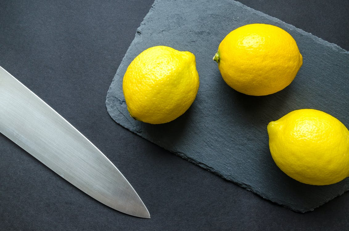 Photo of Three Lemons on Chopping Board Near Knife